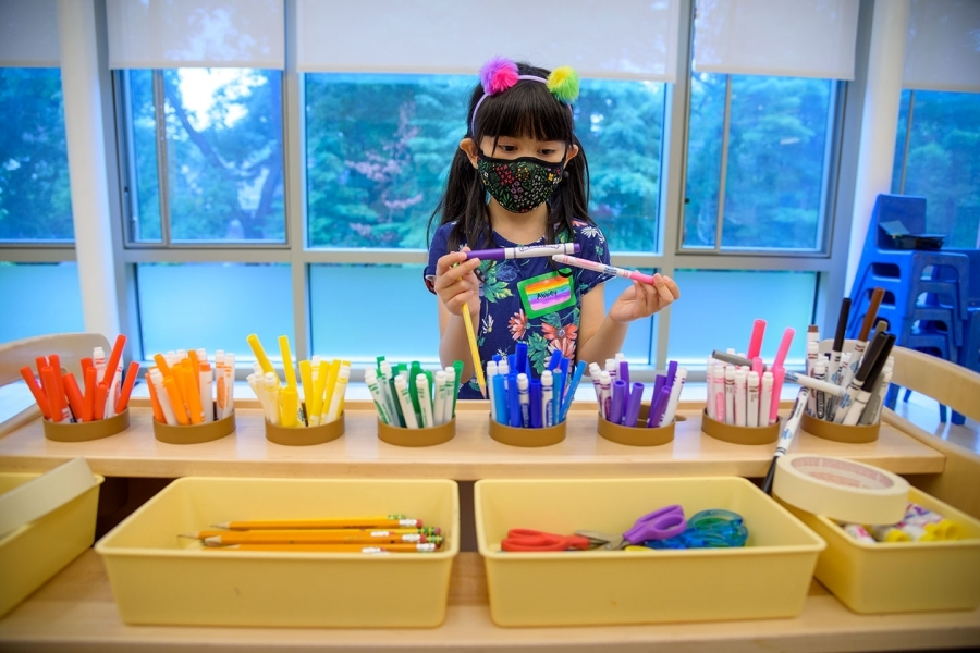 Photo of young girl in school choosing color pens, wearing mask in the time of COVID-19